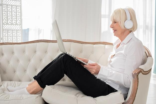 Glückliche alte frau, die auf sofa mit kopfhörern und laptop sitzt