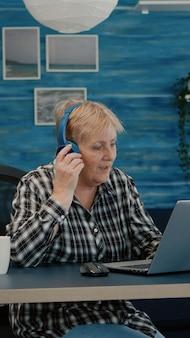 Glückliche alte frau mit kopfhörer, die musik hört, während sie statistiken überprüft