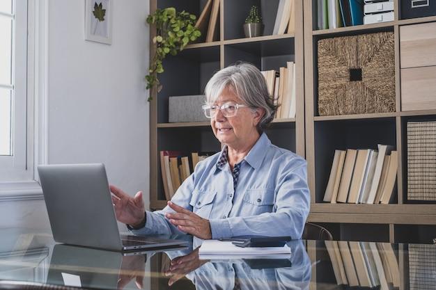 Glückliche alte kaukasische geschäftsfrau, die lächelt, online arbeitet, webinar-podcast auf dem laptop sieht und bildungskurskonferenzen anruft, machen notizen am schreibtisch sitzen, e-learning-konzept
