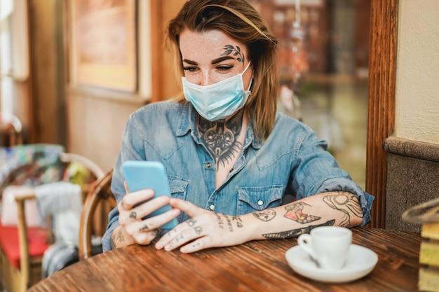 Glückliche alternative frau mit schutzmaske unter verwendung des mobiltelefons an der kaffeebar während des ausbruchs des coronavirus - fokus auf gesicht