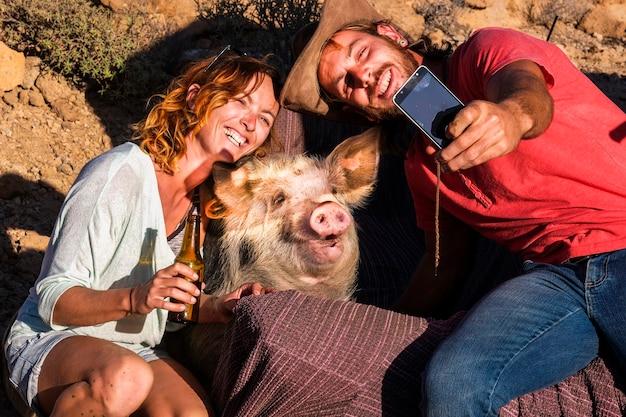 Glückliche alternative natur tierliebhaber paar fröhliche menschen genießen und haben spaß beim fotografieren mit einem lustigen schwein in freundschaft