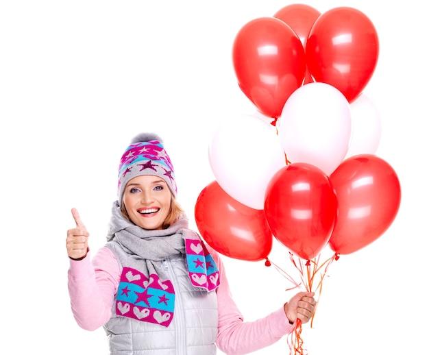 Glückliche amerikanische frau mit roten luftballons und daumen hoch zeichen lokalisiert auf weiß