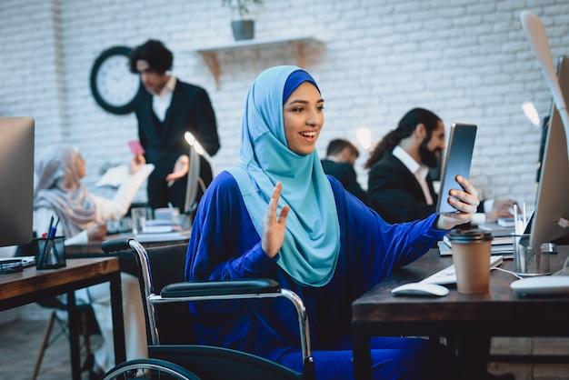 Glückliche arabische dame im rollstuhl macht videoanruf.