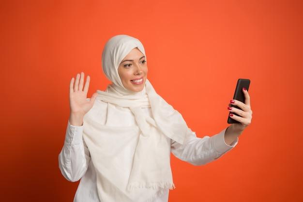 Glückliche arabische frau im hijab mit handy, das selfie macht. porträt des lächelnden mädchens, das am roten studiohintergrund aufwirft. junge emotionale frau. menschliche emotionen, gesichtsausdruck konzept.