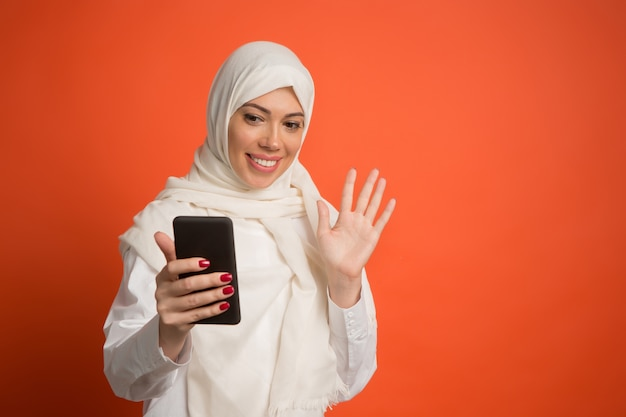 Glückliche arabische frau im hijab mit handy, das selfie macht.