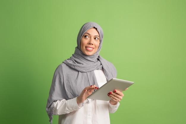 Glückliche arabische frau im hijab mit laptop. porträt des lächelnden mädchens, das im grünen studio aufwirft.