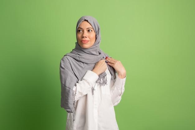 Glückliche arabische frau im hijab. porträt des lächelnden mädchens, das am grünen studiohintergrund aufwirft.