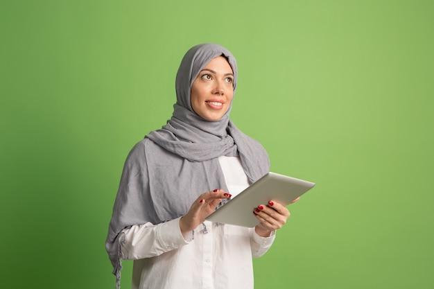 Glückliche arabische frau im hijab. porträt des lächelnden mädchens, das am studiohintergrund aufwirft