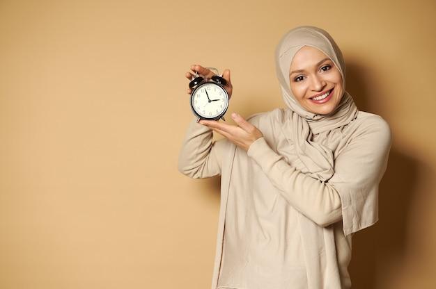 Glückliche arabische frau mit bedecktem kopf im hijab, der wecker in händen hält und niedlich mit zahnigem lächeln vorne lächelt, während er gegen eine beige oberfläche mit kopienraum steht