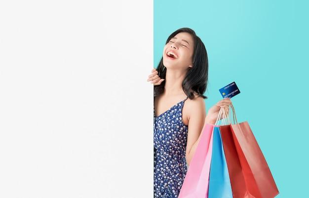 Glückliche asiatin, die einkaufstaschen mit kreditkarte hält und leeres schild zeigt.