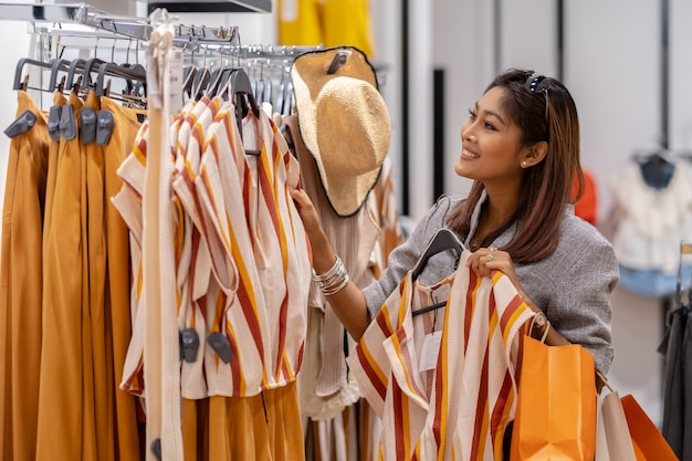 Glückliche asiatin, die kleidung im shopspeicher mit glücklicher aktion in der abteilung mitte wählt