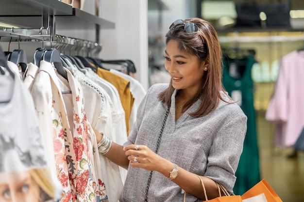 Glückliche asiatin, die kleidung mit in shopshop mit glücklicher aktion in der abteilungsmitte wählt