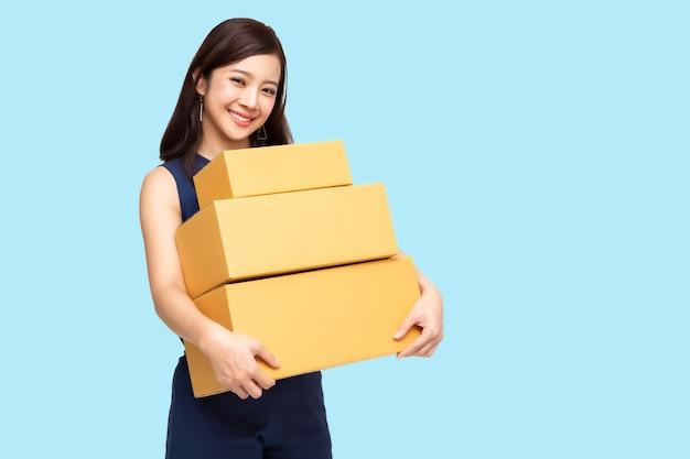 Glückliche asiatin, die paketpaketkasten hält