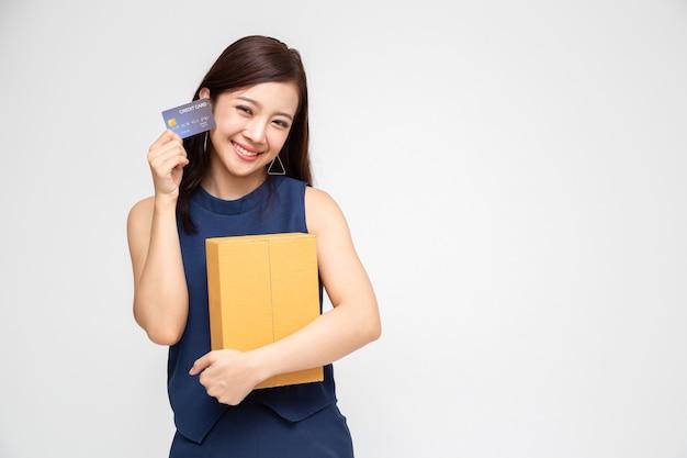 Glückliche asiatin, die paketpaketkasten und kreditkarte, lieferungsversandservice hält und on-line-konzept kauft