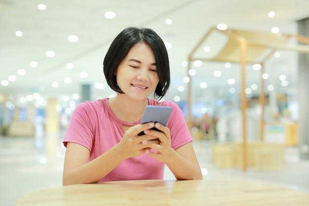 Glückliche asiatin, die smartphone auf tabelle am kaufhaus verwendet