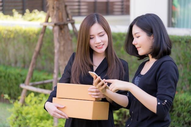 Glückliche asiatin, die smartphone verwendet, um online mit der hand zu kaufen, die deliveried paket hält