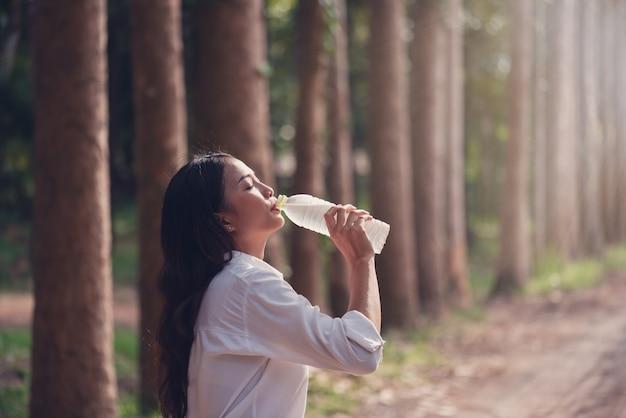 Glückliche asiatin, die süßwasser im wald trinkt