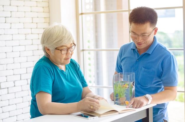 Glückliche asiatische ältere frau, die ein buch liest und konsultiert, sprechend mit ihrem sohn und guter zeit