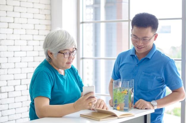 Glückliche asiatische ältere frau, die ein buch liest und konsultiert, sprechend mit ihrem sohn