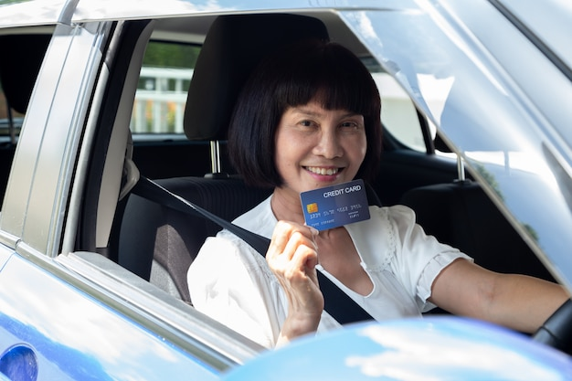 Glückliche asiatische ältere frau, die zahlungskarte oder kreditkarte hält und verwendet, um für benzin, diesel und andere kraftstoffe an tankstellen zu bezahlen, fahrer mit flottenkarten zum auftanken des autos