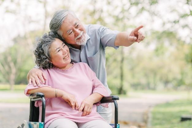 Glückliche asiatische ältere paare, die draußen lächeln