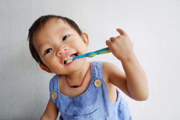 Glückliche asiatische babypraxis, die ihre zähne putzt.