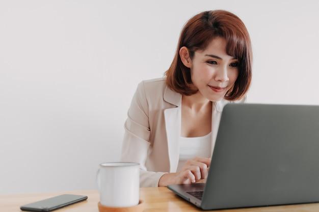 Glückliche asiatische berufstätige frau arbeitet an ihrem laptop im büro