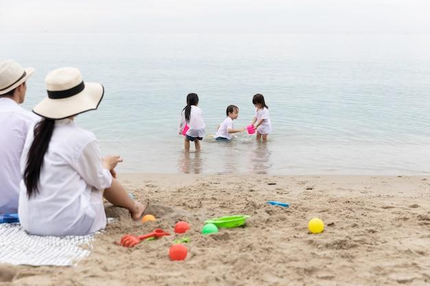 Glückliche asiatische familie bruder und schwester drei spielen morgens gemeinsam spielzeug auf sand am strand. urlaubs- und reisekonzept.