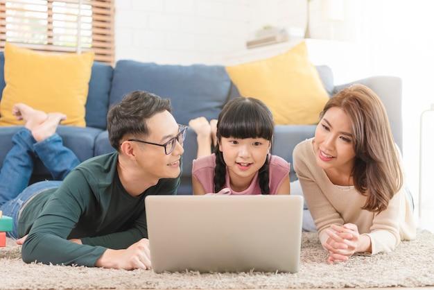 Glückliche asiatische familie, die computer-laptop zusammen auf sofa zu hause wohnzimmer verwendet.