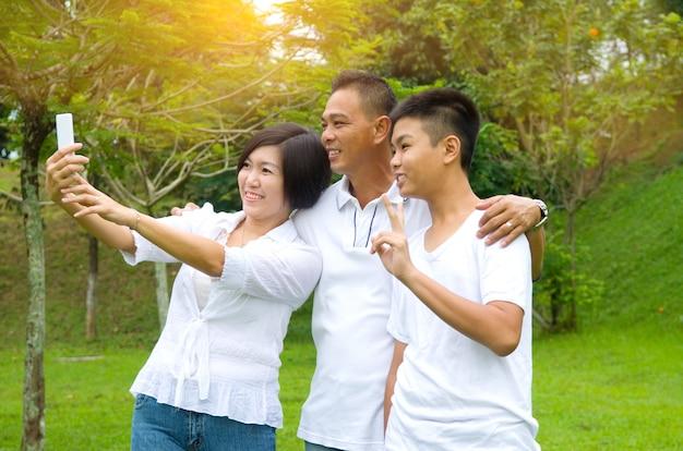 Glückliche asiatische familie, die ein selfie im freien in einem stadtpark nimmt.