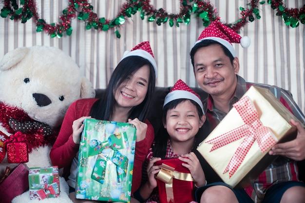 Glückliche asiatische familie, die eine geschenkbox am weihnachtstag hält