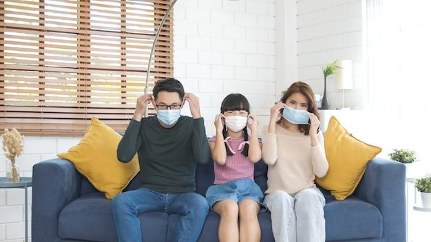 Glückliche asiatische familie, die eine maske trägt, um vor viren im wohnzimmer zu hause zu schützen.