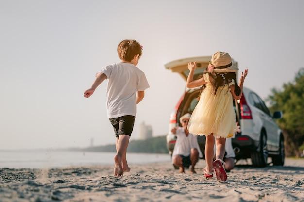 Glückliche asiatische familie, die einen strandausflug mit ihrem lieblingsauto genießt eltern und kinder reisen