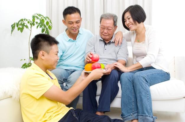 Glückliche asiatische familie, die gesunde frucht isst.