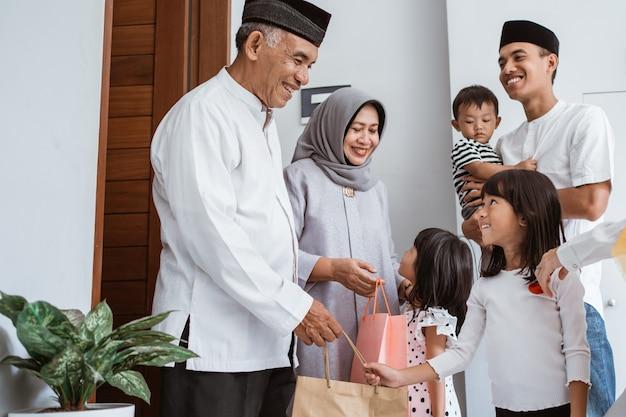 Glückliche asiatische familie, die ihren muslimischen großeltern während eid mubarak feier geschenk gibt. überraschungsgeschenk an die familie