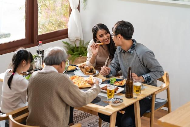 Glückliche asiatische familie, die mittagessen zu hause zusammen isst