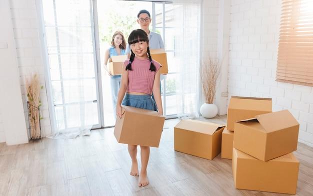 Glückliche asiatische familie, die pappkarton hält, laufen in neues zuhause. umzugskonzept