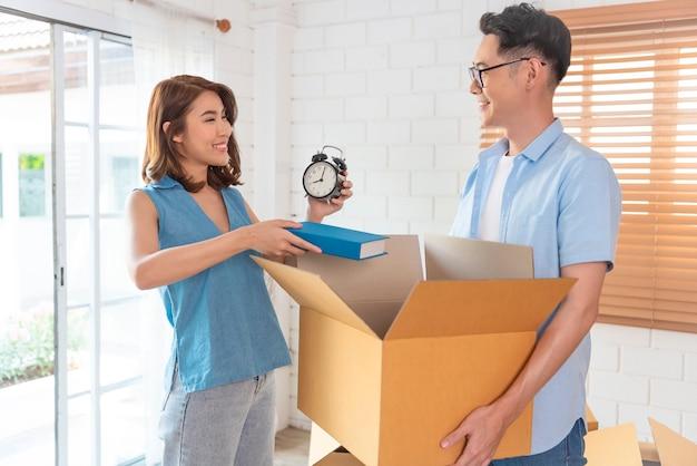 Glückliche asiatische familie, die pappschachtel hält, geht in neues zuhause. umzugskonzept.
