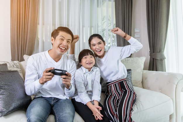 Glückliche asiatische familie, die zu hause videospiele zusammen spielt und spaß hat.