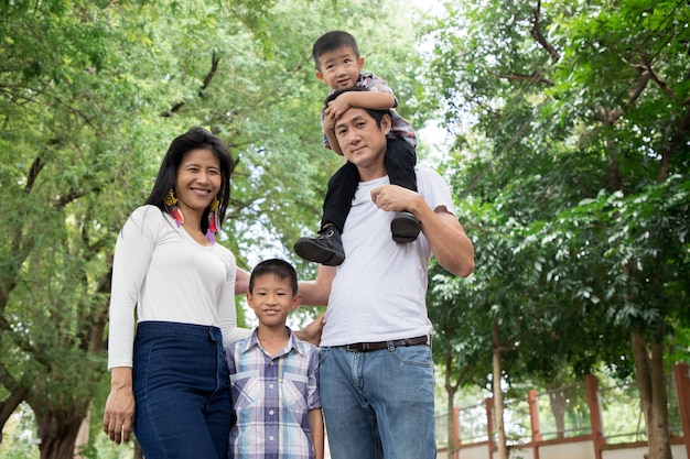 Glückliche asiatische familie, die zusammen familienzeit im park genießt. familienkonzept