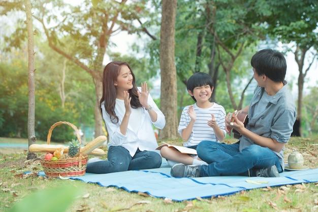 Glückliche asiatische familie haben freizeit im öffentlichen park. vater spielt gitarre mit mutter und sohn klatscht in die hände zusammen mit genuss- und glücksgesicht.