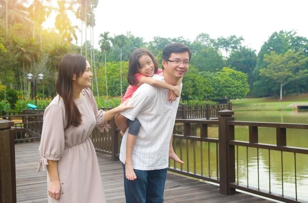 Glückliche asiatische familie im freien. bringen sie seine tochter huckepack tragen, die in gartenpark mit frau geht
