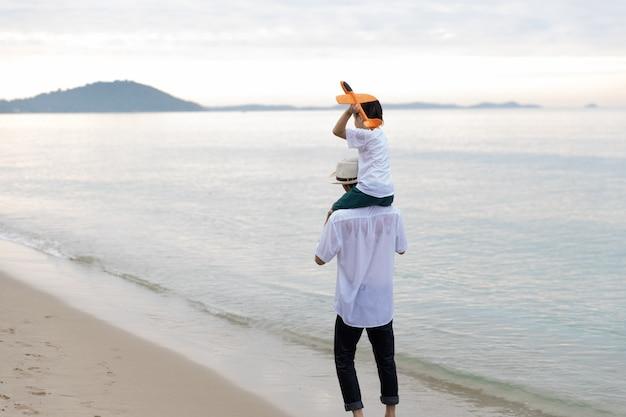 Glückliche asiatische familie im sommerurlaub sohn auf den schultern des vaters, der zusammen fliegendes flugzeug spielt auf dem strand spazieren morgens sonnenaufgang. urlaubs- und reisekonzept.