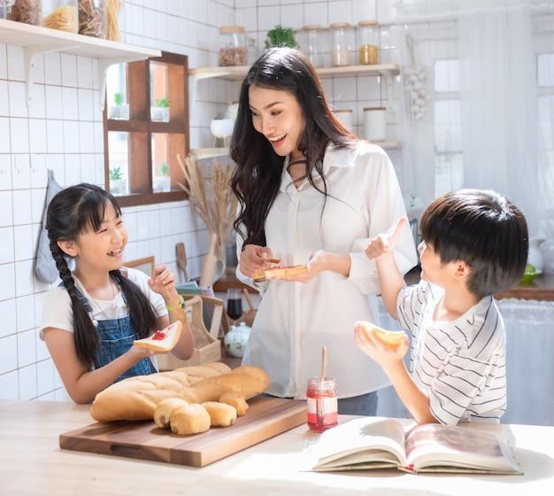 Glückliche asiatische familie in der küche. mutter, sohn und tochter verteilen erdbeer-yam auf brot