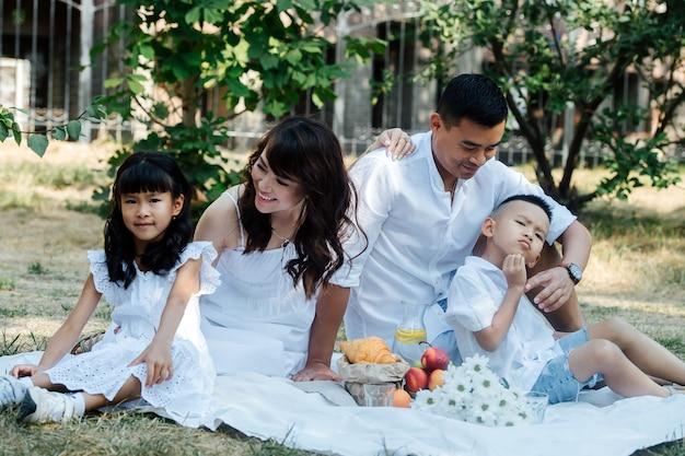 Glückliche asiatische familie in weißer kleidung, die picknick in einem park macht und die letzten warmen tage des frühen herbstes genießt. eltern und ihre kinder in einem baumschatten.