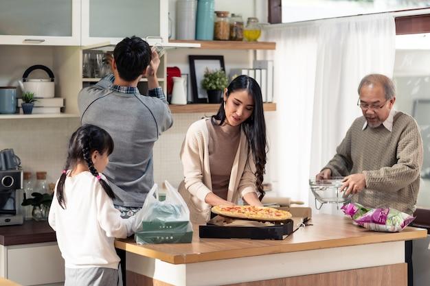Glückliche asiatische familie mit mehreren generationen, die esstisch aufstellt.