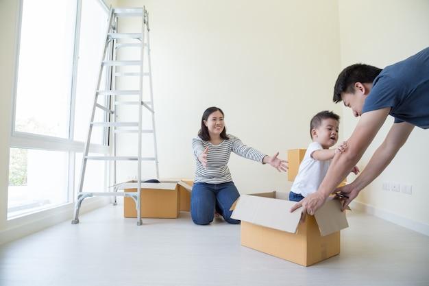 Glückliche asiatische familie mit pappkartons im neuen haus am umzugstag, immobilien- und hauptkonzept