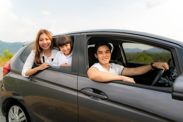 Glückliche asiatische familie mit vater, mutter und tochter im kleinwagen lächeln und fahren für reisen in den urlaub.