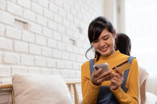 Glückliche asiatische familie online-shopping mit kreditkarte