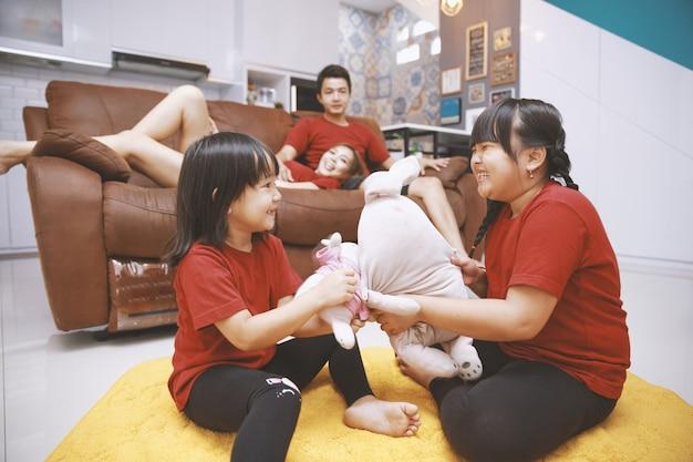 Glückliche asiatische familie verbringt freizeit zusammen im wohnzimmer zu hause das paar sitzt und liegt auf dem sofa und sieht sich zwei kleine tochter an, die puppe auf dem teppich spielt